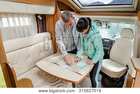 Couples in RV Camper looking at the local map for the trip. Family vacation travel, holiday trip in motorhome, Caravan car Vacation.
