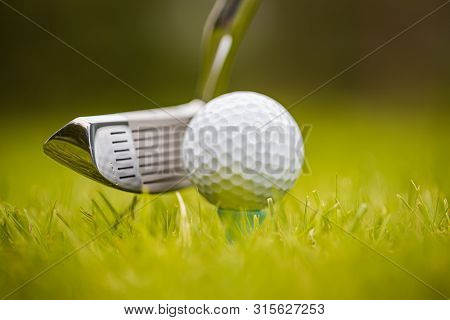 Golf club and ball on tee in front of driver