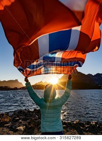 Woman waving the flag of Norway at sunset background