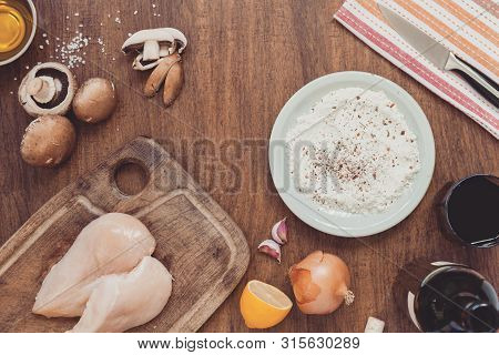 Baking Or Cooking Background Frame. Ingredients For Cooking Chicken With Mushrooms And Onions In Win