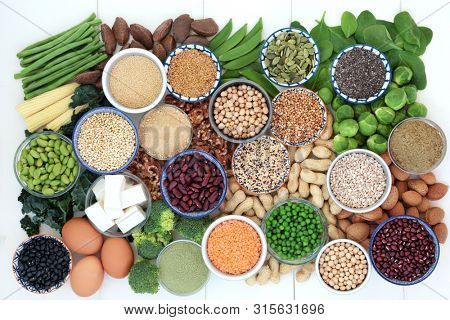 Health food high in protein with bean curd, fresh vegetables, legumes, grains, dairy, supplement powders, seeds and nuts. Super foods high in dietary fibre, vitamins and antioxidants. Top view.
