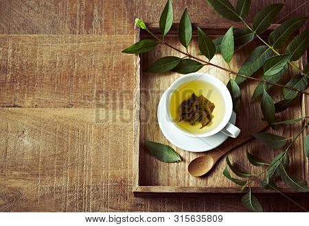 A cup of green tea on wooden tray  with green leaves. Healthy lifestyle. Copy space