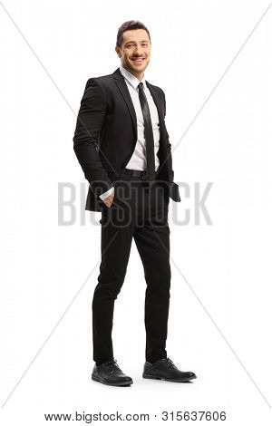 Full length shot of a young man in a black suit posing isolated on white background