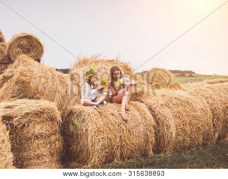 Two teen girls are resting on the haystacks in clear field, in village