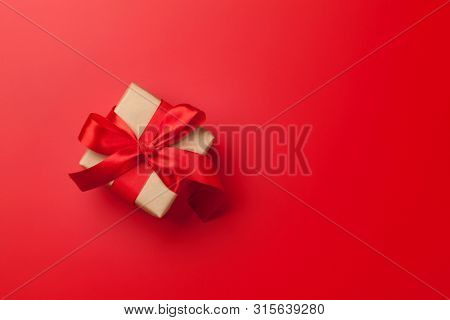 Christmas or Valentine's Day gift box on red background. Top view with copy space