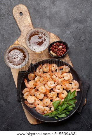 Draft beer and snacks on stone background. Grilled shrimps. Top view with copy space