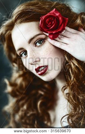 A close up portrait of a lovely mysterious girl with a red rose. Beauty, cosmetics.