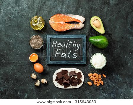 Healthy Fats Sources Concept. Different Food Ingredients And Chalkboard With Ealthy Fats Words On Da