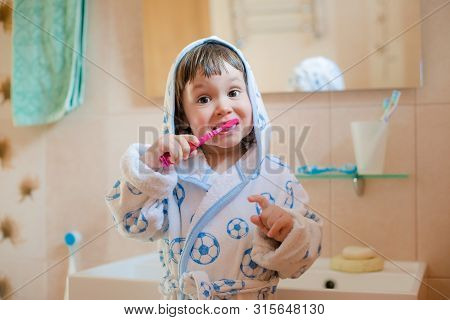 A Little Girl Or Child Brushes Teeth In The Bathroom. Hygiene Of The Oral Cavity. Childrens Toothpas