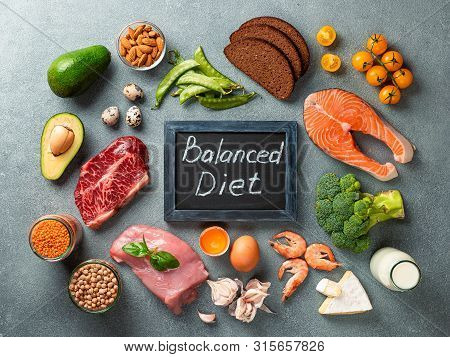 Balanced Diet - Healthy Food On Gray Stone Background. Various Food Ingredients And Chalkboard With