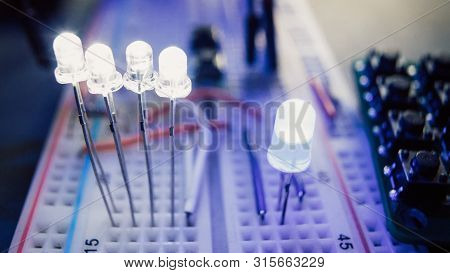 Electrician Inventor Laboratory. Blue Led Light Emitting Diodes On Breadboard Electrical Panel.