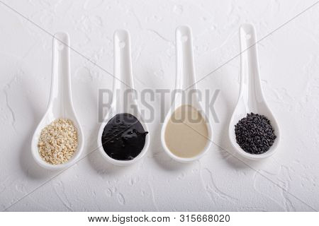 Black Tahini And White Tahini Sauce In Spoons On White Background. Natural Paste Made From Sesame Se