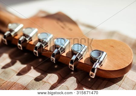 Guitar Headstock Close-up. Guitar Pegs On White Background. Retro Stylized With Shallow Depth Of Fie