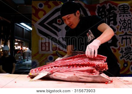WAKAYAMA, JAPAN, MARCH 28, 2019 : A chef is showing how to cut a giant tuna in the Kuroshio fish market