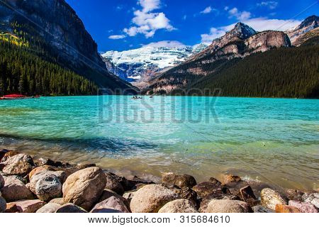 Glacial Lake Louise - the lake with azure water is surrounded by forests and mountains. Rocky Mountains. Red canoes for tourists are moored to the coast. The concept of active and photo tourism