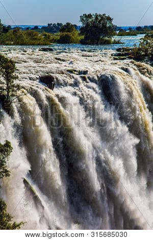 Fantastic walk after the rainy season. Grand Victoria Falls in Zambia. Victoria is a waterfall on the Zambezi River in South Africa.  Concept of active, extreme and photo tourism