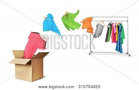 The Concept Of Moving And Transporting Clothes. Clothes Fly Off A Hanger And Fly Into A Cardboard Bo