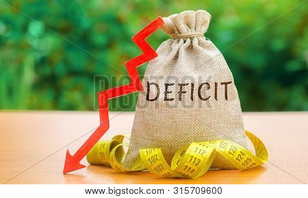 Money Bag With The Word Deficit And Tape Measure With Down Arrow. Budget Deficit Concept. Low Profit