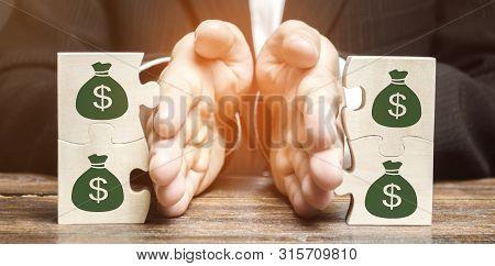 Businessman Separates The Wooden Puzzle With A Picture Of Money. The Concept Of Financial Management