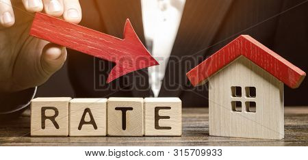 Businessman Holding The Down Arrow On Wooden Blocks With The Word Rate And House. Low Interest In Mo