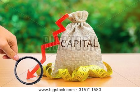 Money Bag With The Word Capital And Arrow Down. Fall In The Level Of Authorized Capital. Drop In Ret