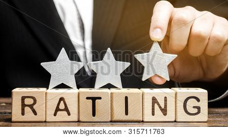 Businessman Puts The Third Star Above The Word Rating On Wooden Blocks. The Concept Of Quality Of Se