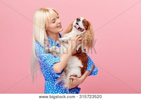 Portrait Of Smiling Young Blond Woman In Summer Hat Embracing King Charles Spaniel Dog. Owner And Pe