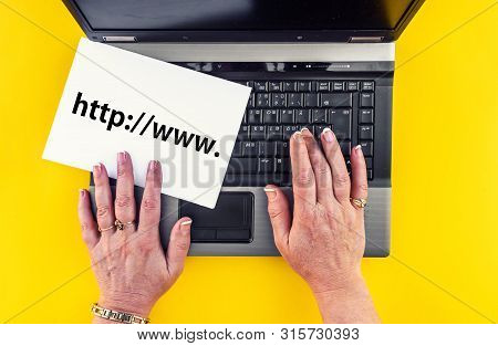 Website Address Or Url Concept. Woman Hands On Laptop And Web Address On Paper Sheet