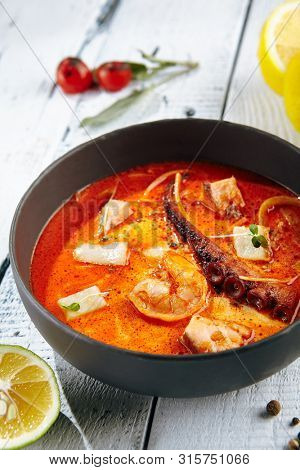 Restaurant Soup Food - Traditional Thai Tom Yam Kung Soup or Tom Yum Kong. Tom Yam is a Spicy Soup with Shrimp and Octopous. Thai Restaurant Soup Menu. Tom Yam Kung on Wooden Background