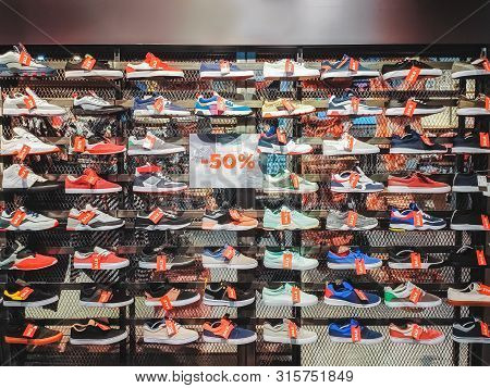 Lots Of Different Sneakers On The Showcase On Market With Tags Sale. Photo Of Sport Shoes On Shop-wi