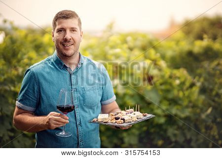 Portrait Of Handsome Young Man Holding Wineglass And Plate Of Cheese And Grapes At Vineyard. Winemak