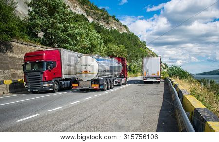 Large Trucks Carrying Different Products, On A Beautiful Mountain Road, On A Summer Day. Near The Ro