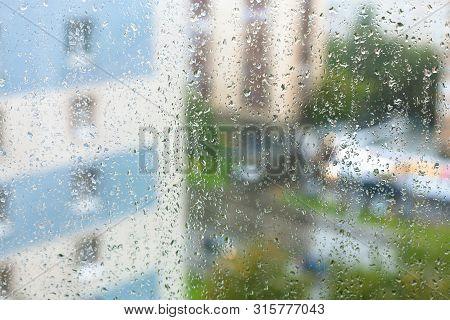 Rain Drops On Windowpane And Blurred City On Background On Rainy Autumn Evening
