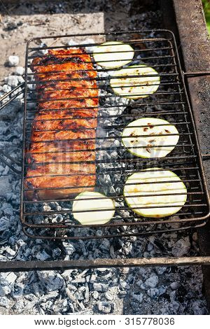 Cooked Pork Ribs With Sliced Squash Vegetable In Outdoor Charcoal Grill