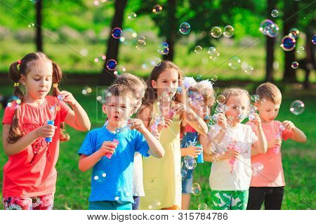 Group Of Children Blowing Soap Bubbles In A Garden
