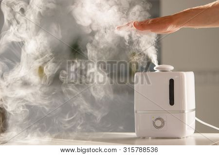 Man Holds Hand Over Steam Aroma Oil Diffuser On The Table At Home, Steam From The Air Humidifier, Fr
