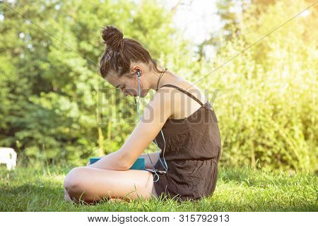 Teenage Girl Hears Music In A Garden And Reading