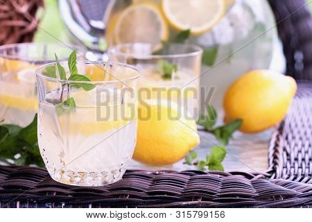 Glass Of Cool Refreshing Southern Lemonade With Mint And Fresh Lemons Setting On A Table Outdoors.