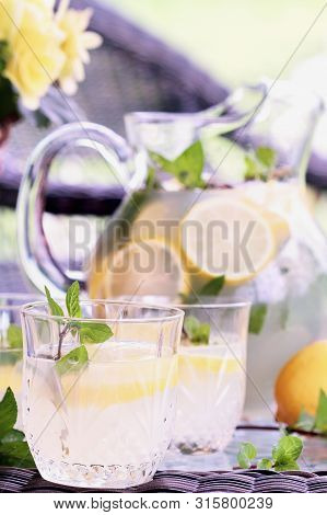 Glass Of Cool Refreshing Southern Lemonade With Mint Setting On A Table Outdoors.