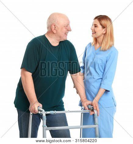 Caretaker Helping Elderly Man With Walking Frame On White Background