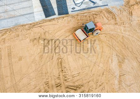 Road Roller At Construction Site. Leveling Sand Before Road Construction Works. Aerial Photo