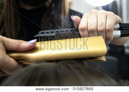 Cute Girl With Long Brunette Hair Hairdresser Doing Hair Lamination In A Beauty Salon. Concept Of Ha