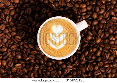 Fresh Roasted Coffee Beans Background With Cup Of Coffee With Latte Art.