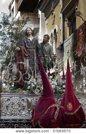 Couple of penitents with a Holy Week image during a procession in Jumilla (Spain) poster