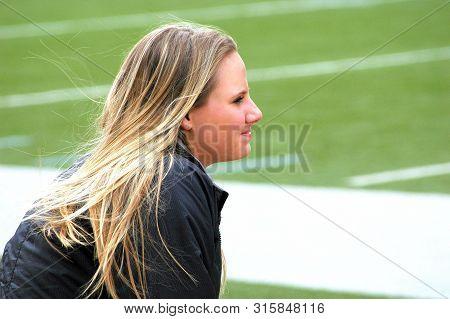 Seattle, Wa. April 6, 2006. Circa:  Female Captain Cheerleader Sitting On The Football Field Sidelin