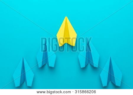 Leadership Concept With Paper Planes Over Turquoise Blue Background With Copy Space. Top View Of Yel