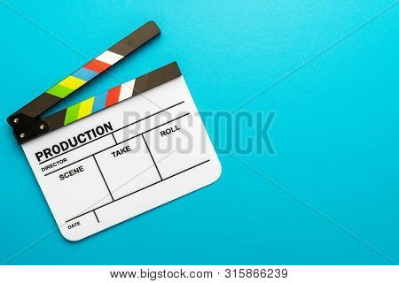 Top View Photo Of Open White Clapper Over Turquoise Blue Background. Minimalist Shot Of Clapper With