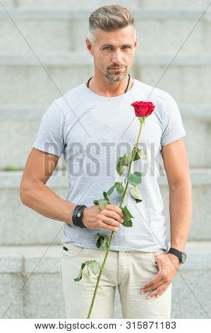 The Celebration Of The Special Holiday. Handsome Man Holding Red Rose For Holiday Celebrating. Cauca