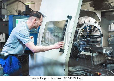 Worker man operating a CNC lathe in factory