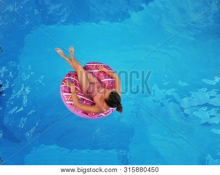 Young Beautiful Girl Relaxing And Swimming In The Blue Swimming Pool With A Pink Circle Closeup